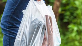 A consumer carrying plastic shopping bags